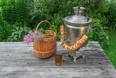 Rosyjski samowar na nieociosanym drewnianym stole z jagodami i kwiatami Obraz Stock