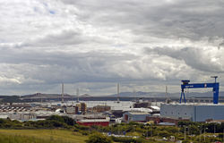 Rosyth dockyard. With the three bridges across the forth river in the background . In the foreground is the aircraft carrier Prince of Wales is covered in stock photo