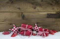 Rot überprüfte Weihnachtsgeschenke auf hölzernem Landhausstil backgroun Lizenzfreies Stockfoto