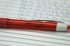 Rot ballpen auf weißem Notizbuch Stockfotos