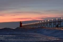 Rot beleuchteter Leuchtturm und Pier an der Dämmerung Lizenzfreie Stockbilder