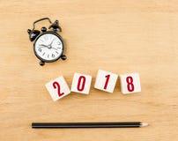 Rot des neuen Jahres 2018 auf hölzernem Würfel mit Draufsicht des Bleistifts und der Uhr an Stockfoto