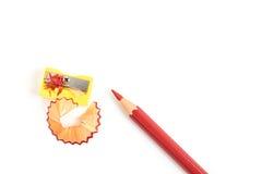 Rot färbte Bleistift mit dem Bleistiftspitzer, der auf weißem Hintergrund lokalisiert wurde Lizenzfreies Stockbild