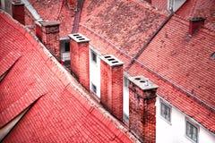 Rot farbige alte mit Ziegeln gedeckte Dächer Stockbild