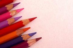 Rot farbige Bleistifte über einem rosa Hintergrund stockbilder