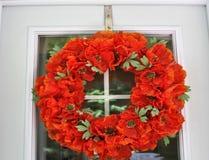 Rot geblühter Kranz auf Tür stockbilder
