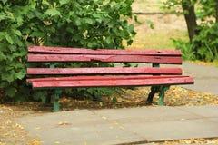 Rot gemalte alte Holzbank im Park Lizenzfreies Stockbild