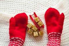 Rot gestrickter Handschuhschlitten und goldene Geschenke Das Konzept von Weihnachten Stockfotografie
