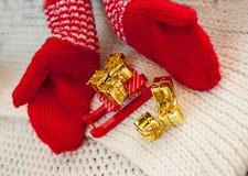 Rot gestrickter Handschuhschlitten und goldene Geschenke Das Konzept von Weihnachten Stockbilder