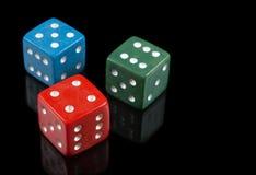 Rot, Grün und Blau würfelt auf schwarzem Hintergrund Stockfotografie