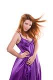 Rot-haariges Mädchen in einem purpurroten Kleid Stockfoto