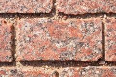 Rot mit Streifen des Granitziegelsteines in der Maurerarbeit Stockfotografie