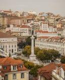 Rot-mit Ziegeln gedeckte Dächer und eine Statue in Lissabon, Portugal Stockfotografie