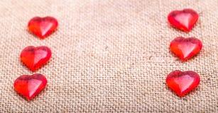Rot mit zwei Reihen das stekyannykh von Herzen auf einer Serviette von einem sackin Stockfotografie