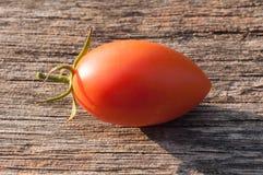 Rot-orange, kleine Tomate auf einem hölzernen Hintergrund stockbild