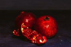 Rot schnitt Granatapfel auf einem blauen Abstraktionshintergrund Lizenzfreie Stockfotos