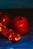 Rot schnitt Granatapfel auf einem blauen Abstraktionshintergrund Lizenzfreie Stockbilder