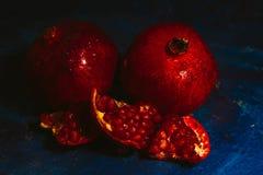 Rot schnitt Granatapfel auf einem blauen Abstraktionshintergrund Stockfotografie