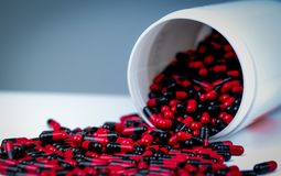 Rot-schwarze antibiotische Kapselpillen werden aus weißem Plastikflaschenbehälter heraus verschüttet viele Flaschen Medizin Versc stockbild