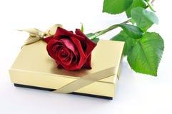 Rot stieg auf einen goldenen Geschenkkasten Stockfotografie