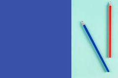 Rot und Blau färbten Bleistifte auf blauem Farbhintergrund Stockfotos