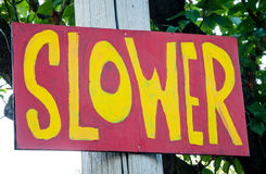 Rot und Gelb gemaltes Zeichen auf der Nachbarschafts-Straße LANGSAMER Lizenzfreie Stockfotos