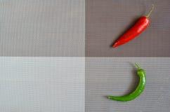 Rot und grüne Paprikas auf einem rechteckigen Hintergrund des Graus, des Brauns und des spanischen Pfeffers auf einem rechteckige Stockfoto