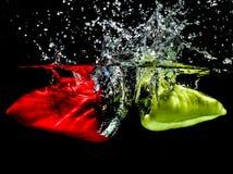 Rot und grüne Paprikas, die Wasser spritzen lassen Lizenzfreies Stockbild