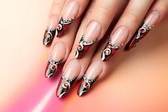 Rot- und Kunstdesign auf Nägeln stockbild