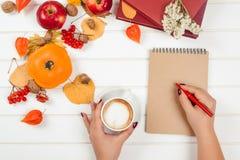 Rot und Orange färbt Efeublattnahaufnahme Weibliche Handschrift im Notizbuch nahe Schale Cappuccino Lizenzfreie Stockfotos