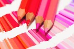 Rot und Rosa färbten Bleistifte und Farbdiagramm aller Farben Lizenzfreie Stockfotos