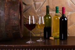 Rot und Weißwein neben alter Tonne im Weinkeller Lizenzfreie Stockfotos