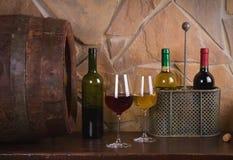 Rot und Weißwein neben alter Tonne im Weinkeller Stockfotografie