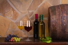 Rot und Weißwein neben alter Tonne im Weinkeller Lizenzfreie Stockfotografie