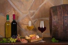 Rot und Weißwein neben alter Tonne im Weinkeller Lizenzfreies Stockfoto