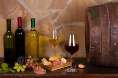 Rot und Weißwein neben alter Tonne im Weinkeller Stockfoto