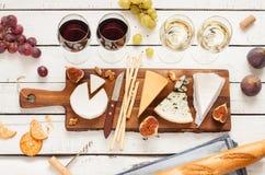 Rot und Weißwein plus verschiedene Arten von Käsen (cheeseboard) Stockbild