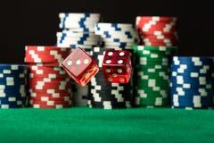 Rot würfelt in einer Luft und in den Pokerchips Stockbilder
