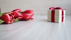 Rot-weiße Tulpen und Geschenkbox mit Bogen auf weißer Tabelle stock video footage