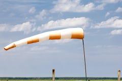Rot-weißer Windsock, der Wind mit blauem Himmel am Flugplatz anzeigt Lizenzfreie Stockfotos