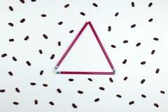 Rot zeichnet Dreieckrahmen mit roten Bohnen auf weißem Hintergrund an Stockfoto