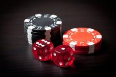 Rot zwei würfelt und schwarze und rote Chips Stockfotos
