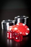 Rot zwei würfelt und schwarze und rote Chips Stockfotografie