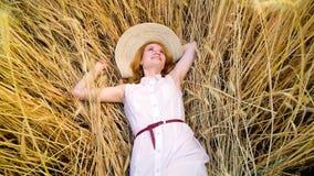 Rotação da câmera sobre a mulher de cabelo vermelha nova que encontra-se no campo de trigo e que tem o resto filme