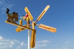 Rotação de uma aleta de tempo de madeira com figuras dos povos e das lâminas pintadas contra foto de stock royalty free