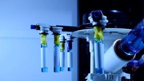 A rotação lenta do dispositivo para analisa tubos de ensaio médicos com solvente azul video estoque