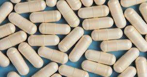 Rotación blanca médica de las píldoras en fondo azul almacen de metraje de vídeo