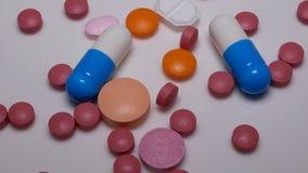 Rotación de píldoras y de tabletas en el fondo blanco almacen de video