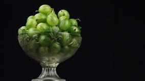 Rotación de un montón de grosellas espinosas verdes en un florero de cristal almacen de metraje de vídeo