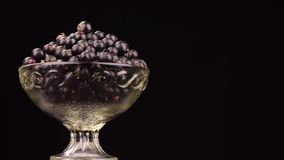 Rotación de un montón de grosellas negras en un florero de cristal metrajes